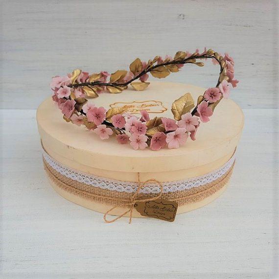 Corona de flore de porcelana en colores rosados y dorado.