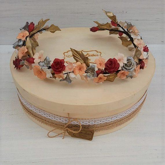 Corona de flores con rosas rojas con toque de dorado y plata.