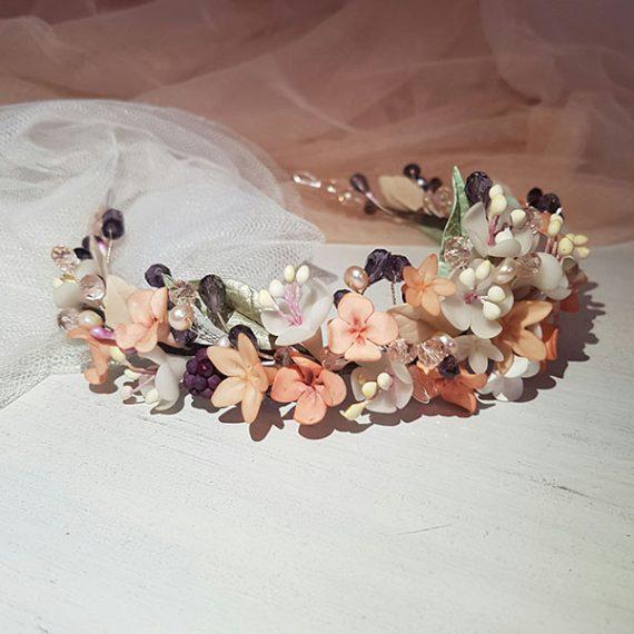 Corona de flores y cristales de colores suaves.